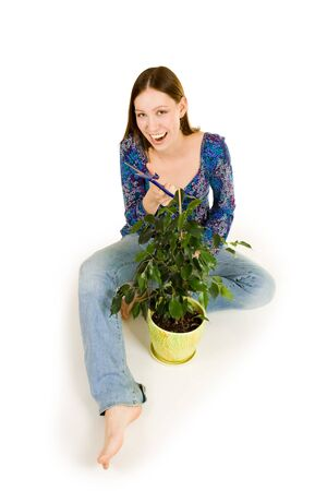 Woman on the floor cutting plant with blue scissors