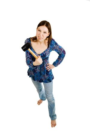 Aggressive woman holding hammer in her hand and looking straight Stock Photo