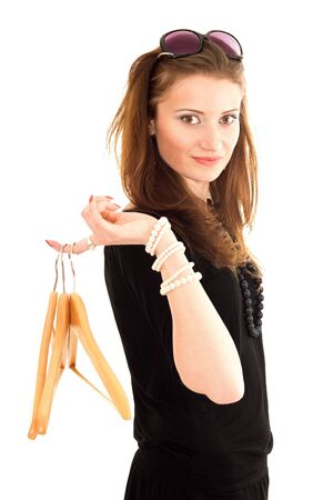 hook like: Young woman shopping, holding hanger on finger looking to camera and standing in profile Stock Photo