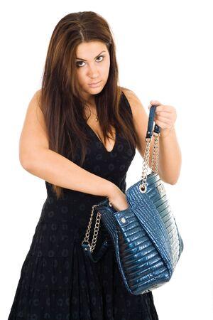 Mujer joven con pelo largo buscando algo en su bolso con la mano en su bolso de color azul claro mirando a la cámara