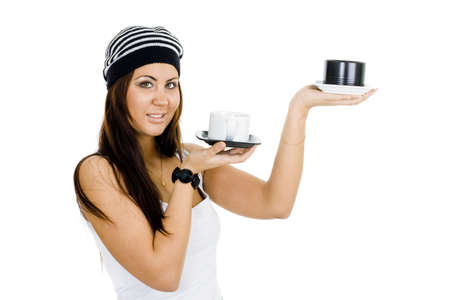 woman holding black and white cups like balance in white top and black pants photo
