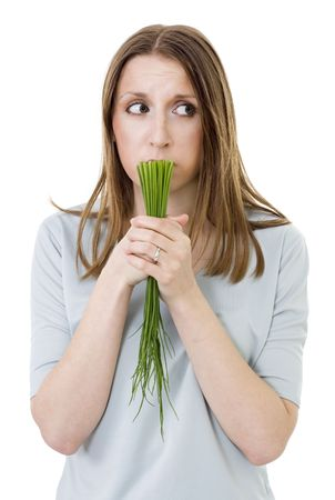 woried woman with onion holding bunch green onion photo