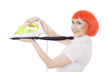 happy woman flattening tie with green iron in profile with red hair photo
