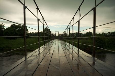 suspension bridge after rain over moscow river, countryside. made of wood and wire photo