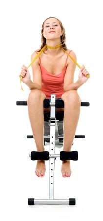 centimetre: Happy young woman sitting on bench for fitness with centimetre isolated on white