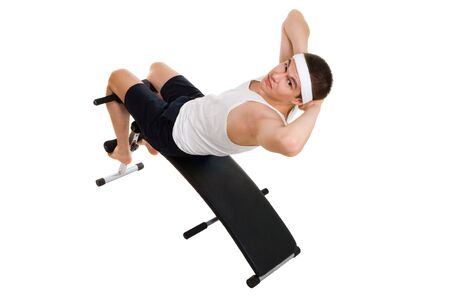 Young man exercise on bench working on abdominal muscles isolated on white Stock Photo - 5412035