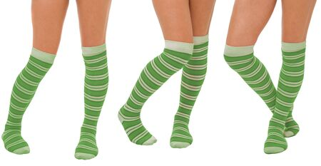 Pairs of women legs in color green socks standing in different poses isolated on white photo