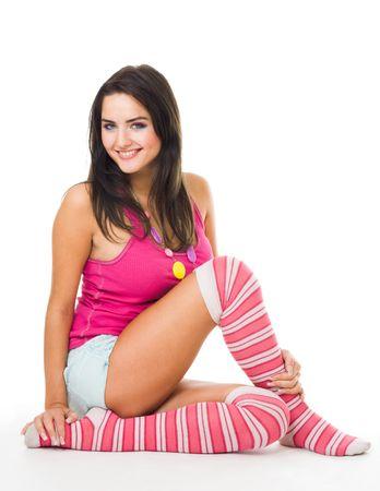 calcetines: La mujer en los calcetines de color rosa con el pelo largo sentarse y mirar a la c�mara, vista lateral, aislado en blanco Foto de archivo