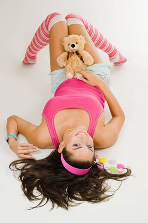 Beautiful young woman lay on white floor in vivid pink clhothes with toy photo