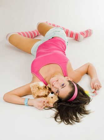 Young woman in pink color clothes lay on thw floor and smile with toy Stock Photo - 5445873