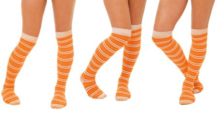 Pairs of women legs in color orange socks standing in different poses isolated on white photo