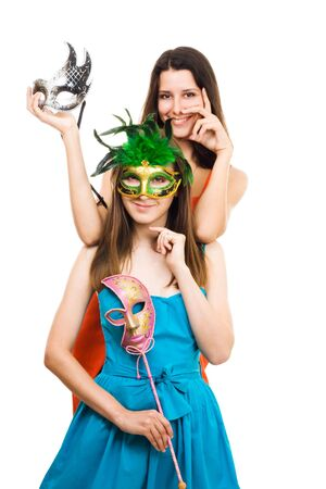 Two positive young women with mask at masquerade party, isolated white photo