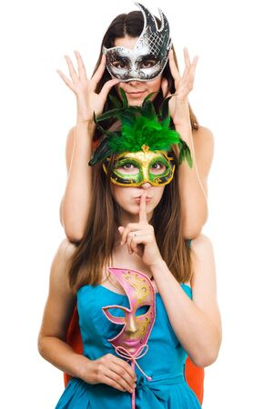 sh: Two young women in masks make hush sign,isolated on white