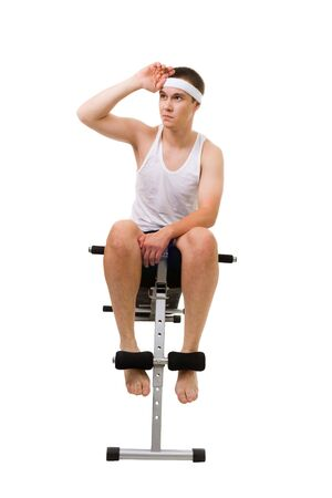 Young man sit on bench for fitness and rest, isolated on white photo