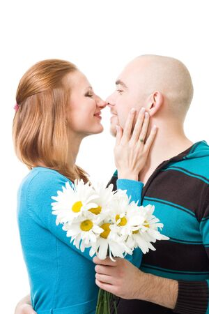 Couple kissig standing holding flowers standing in profile,isolated on white photo