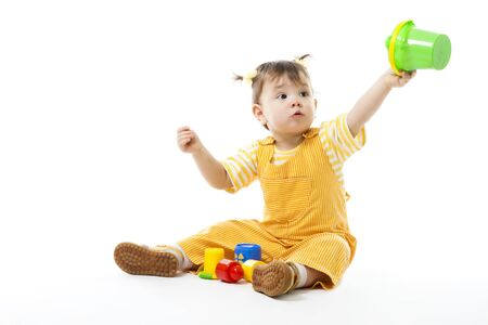 Kid play sit and with toys, holding pail,isolated on white photo