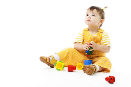 Kid sit and play with toy, dressed in yellow pyjamas, isolated on white photo