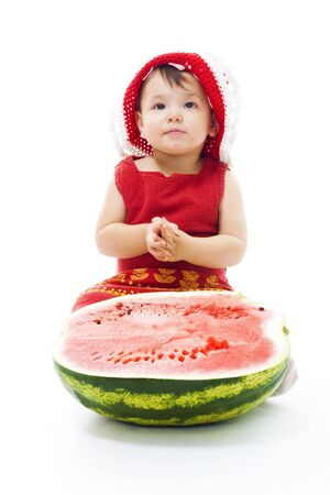 Baby with red dress and cap sit with half of watermelon,isolated on white photo