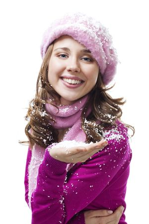 Woman blow snowflakes from palm, look at camera and smile photo