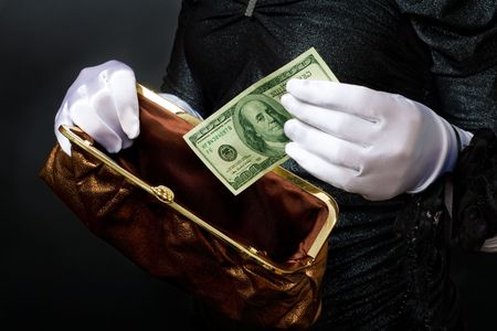 Woman in white gloves put dollars in purse Stock Photo - 5861429