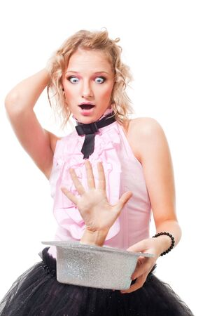 Beautiful woman illusionist perform scary trick getting hand from hat, isolated Stock Photo - 6121666