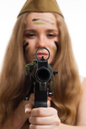 Woman look at camera through gun sight with camouflage on her face photo