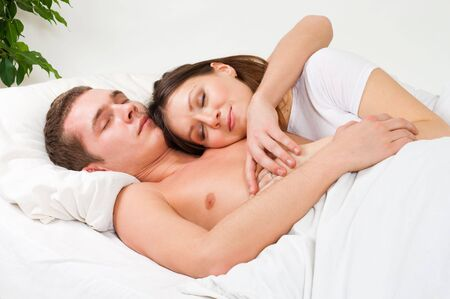 Couple sleep in the bed and and smile in home interior photo