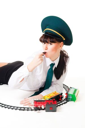 Attractive woman railway worker blow in whistle and crashed toy train photo