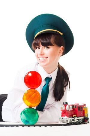 Young woman, railroad dispatcher with traffic light and toy locomotive photo