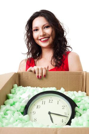 carefully: Happy woman holding box with clock carefully packed