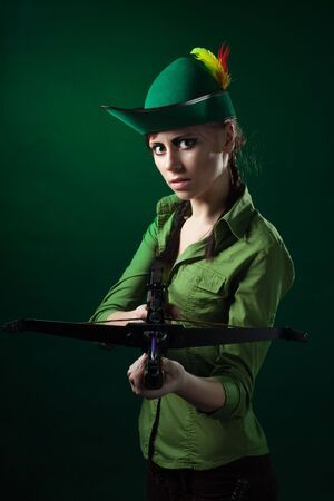 Serious woman frowning holding crossbow and aiming photo