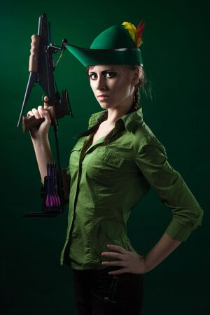 Robin hood style woman hold crossbow ready to fight photo