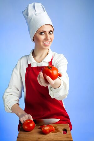 Happy smile  woman chef offer tomatoes on blue background photo