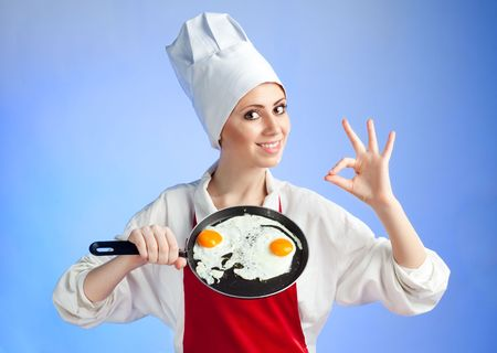 Chef with pan and frying egg ready to serve breakfast photo