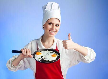 Chef stand with frying egg and pan with big smile and thumb up photo