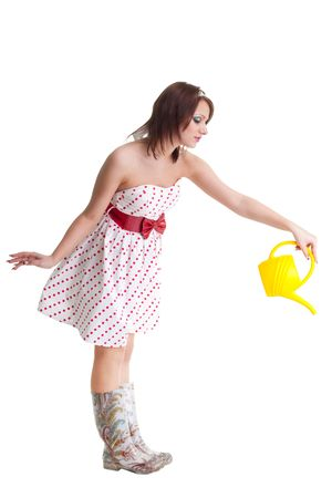 solicitous: Young woman watering with water can, standing isolated on white