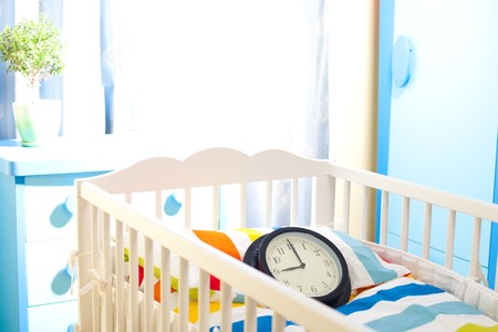 Nursery room with baby bed and clock counting time for new owner Stock Photo - 7254263