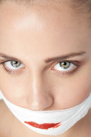Face of a girl after plastic surgery with bandage on her face photo