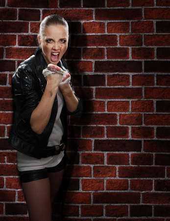 Angry street girl fighting on the brick wall background photo
