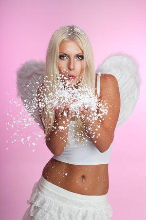 blow: Angel colpo fuori la neve dalle sue mani con le ali in rosa  Archivio Fotografico
