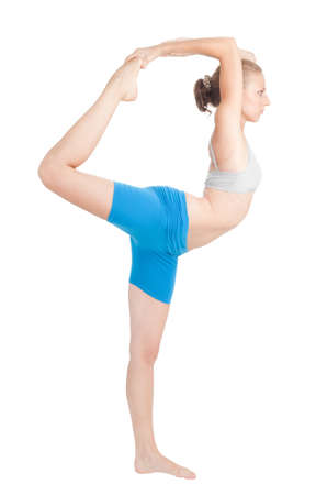 short shorts: Woman exercise in flexibility standing in profile and holding leg with hands