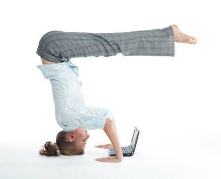 flexible: Attractive woman browsing on laptop in unusual yoga pose heels over head