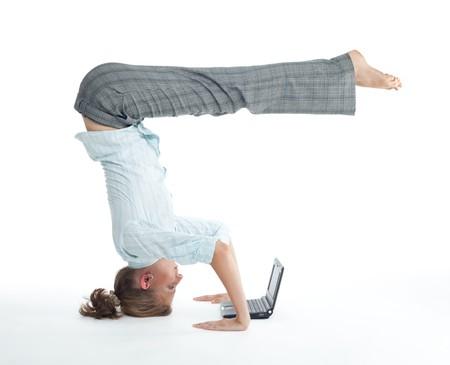 Attraktive Frau, die das Surfen auf Laptop in ungewöhnlichen Yoga-Pose heels über Kopf