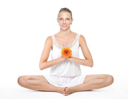Young woman in white sitting in yoga pose and meditating photo