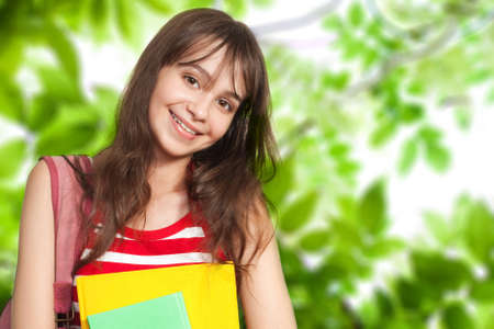 supercilious: Teenage girl with books outside under green trees Stock Photo