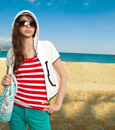 supercilious: Stylish teenager on a shore wearing shades and looks arrogant