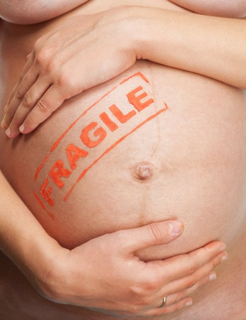 Handle with care - pregnant womans belly with fragile sigh photo