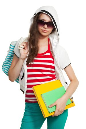 Stylish teenage girl wearing shades standing with books