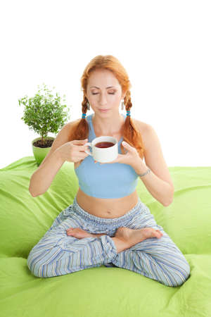 Smelling tea aroma - woman sitting in yoga pose at home in the morning and drinking tea photo