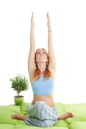 hair do: Young happy woman with red hair do yoga exercises at home